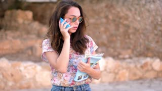 Woman looking map and talking phone in slow motion. Close up of female tourist talking mobile. Girl speaking phone and search route. Smiling girl talk mobile