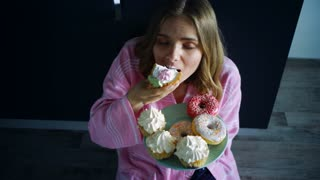 Woman overeat sweet cupcake on kitchen table. Hungry woman eating dessert. Happy girl enjoy cream cupcake at night. Calories food addiction. Night eating