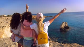 Woman party at Cyprus rocky coast. Back view of girls have fun at rocky cliff. Four women fun in the beach. Vacation beach party. Happy woman enjoy life at ocean cliff