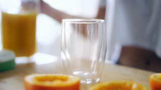 Woman pouring orange juice from glass jar into glass. Close up glass of fresh orange juice. Preparing healthy breakfast from natural ingredient. Homemade fruit juice on table. Organic vitamin drink