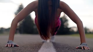 Woman push up exercise. Sporty woman pushing on asphalt road. Closeup of sport woman pushing outdoors. Push ups exercise in slow motion. Close up of fitness woman push up on park road. Outdoor workout