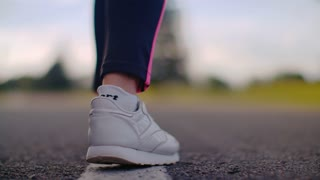Woman runner start to run. Close up of runner legs in white sneakers on asphalt road. Female athlete feet start to run in running shoes. Close up of runner feet in running shoes on road