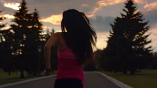 Woman running at sunrise sky background. Running woman silhouette in slow motion. Woman running in park at morning. Morning fitness training. Fitness woman running away on road at sunrise