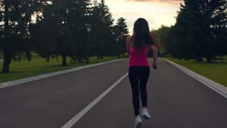 Woman running away in park. Young woman running at morning. Morning fitness training. Female jogger in park. Fitness woman running on road. Running woman in slow motion.