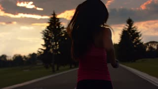 Woman running in park at sunset. Back view of running woman at evening in park. Fitness woman jogging on park road at sunset. Running woman silhouette in slow motion at sunset sky background