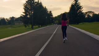 Woman running in slow motion. Running woman on park road. Sporty woman jogging. Fitness woman running outdoors. Back view of female runner. Fit girl running at morning. Fitness workout outdoor
