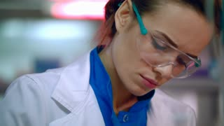 Woman scientist portrait. Female scientist face close up. Serious scientist woman working. Medical scientist thinking. Lab woman face in safety glasses. Female lab technician working
