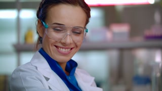 Woman scientist smiling. Happy scientist portrait in safety glasses. Scientist face. Female lab scientist smile. Closeup of lab woman happy face. Happy researcher in lab. Lab woman smiling