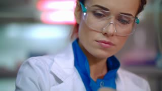 Woman scientist working with liquid in science lab. Close up of female scientist doing laboratory research. Scientist face at research lab. Scientist cure. Lab worker researching liquid in lab flask