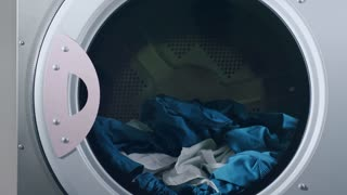 Woman take away uniform from dryer machine. Close up of washed clothes in industrial washing machine. Worker doing laundry. Industrial dryer laundry. Clothes dryer machine
