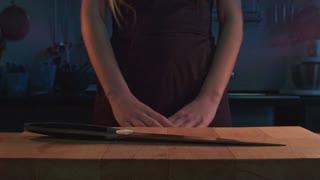Woman take knife on kitchen. Knife killing concept. Woman knife killer. Woman hands take kitchen knife on wooden board