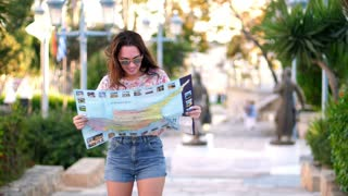 Woman tourist looking map at Cyprus. Beautiful woman in sunglasses looking route on map in tropical city. Close up of female tourist look map