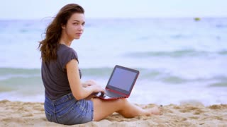 Woman working with laptop on seashore. Female freelancer working near sea. Using modern technologies. Business and vacation concept. Woman freelancer with laptop on beach
