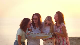Women laughing together on sunset beach. Female tourist group have fun with route map at evening seashore. Happy women planning journey. Laughing people traveling. Enjoy Cyprus vacation