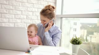 Working woman with baby speaking phone. Business mom with child talking on mobile. Smiling mother with kid working in cozy home studio. Mother working with little girl. Mom have conversation on phone