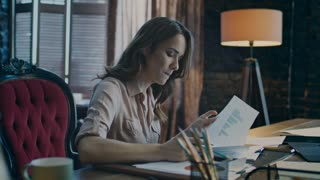 Worried business woman thinking in office at evening. Focused businesswoman working with document. Female worker learning bad business statistic. Concentrated woman reading papers in office