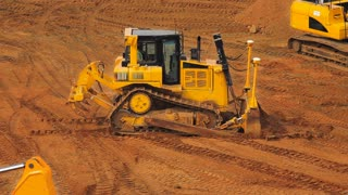 Yellow crawler bulldozer in mining quarry. Heavy machinery in mining industry. Excavator moving soil. Earth moving equipment working at quarry. Preparing building area for road construction