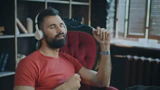 Young bearded man sitting in chair listening to music in headphones incredibly feeling rhythm of music and snapping fingers. Music inspiration at work