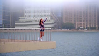 Young beautiful woman waving goodbye. Girl waving somebody in the sea. Girl standing on embankment under water and seeing off someone. Happy woman waving and smile