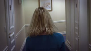 Young blonde woman in blue dress walking on hallway corridor at guest hotel. Close up woman walking in room number in corridor back view