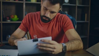 Young business man working with pen with business documents in office at evening. Portrait of handsome businessman analyzing charts and making notes. Business analysis of financial report