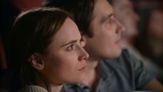 Young couple dissapointed while watching film in movie theater. Pretty girl watching thrilling movie at cinema. Close up of woman watching melodrama with boy in slow motion
