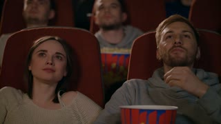 Young couple enjoying film in cinema. Couple eating popcorn in slow motion. Guy and girl watching movie in cinema. Girl sharing her impressions while watching movie with guy. Cinema couple relax