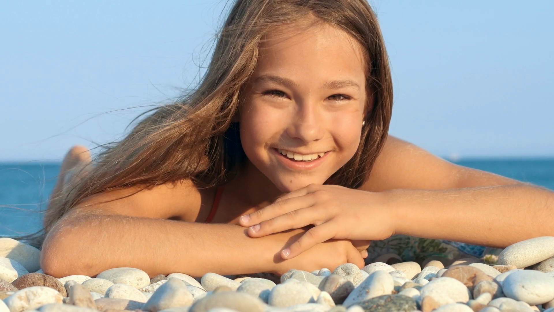 Young girl smiling on sea beach. Portrait of smiling girl