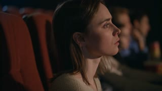 Young girl thoughtfully watching film at cinema. Pretty woman face watching thrilling movie at cinema. Young woman looking thoughtfully performance in theater. Female spectator of cinema
