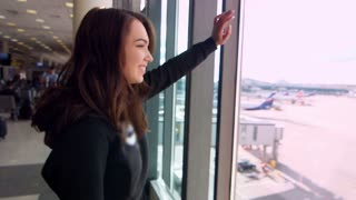 Young girl waving hand at window saying goodbye at airport. Brunette woman saying goodbye flying away plane. Pretty woman smiling and looking from window of airport