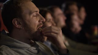 Young guy eating popcorn in slow motion. Young man laughing in movies theater. Hipster man eating popcorn in cinema. Close up of man watching comedy film
