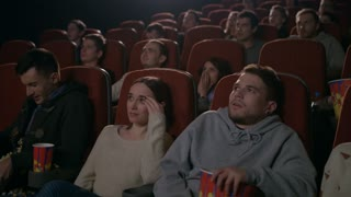 Young guy scared while watching horror film in movie theatre. Young man sprinkling popcorn in slow motion at cinema. Spectators frightened by horror film. People watching scary movie