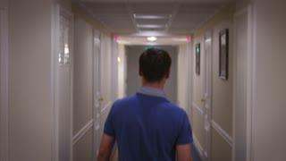 Young man in blue shirt walking along corridor at hallway hotel back view. Man walking on light corridor in cozy hotel interior