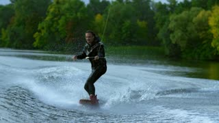 Young man on wakeboard dissecting river waves in slow motion. Wake skier making tricks on waves during movement. Extreme holidays. Adventurous summer holidays at river. Wake boarding sport