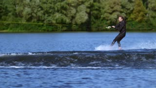 Young man rushing on water board on water behind motorboat. Extreme water sports. Wakeboarder training in lake. Active guy enjoying his vacations. Rider wakeboarding on wave. Extreme lifestyle