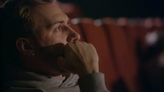 Young man talking on phone at cinema. Man talking on mobile phone in movie theatre. Close up of man speaking phone at movie hall. Spectator speaking phone in cinema
