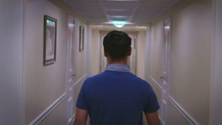 Young man walking along hallway corridor at home interior back view. Man back view walking on long corridor in cozy hotel