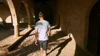 Young man walking among dark ancient rooms in slow motion. Man walking in historical building back view. Visiting historical places. Guy going inside old building with shadows. Male tourist