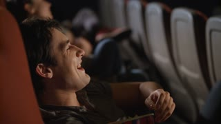 Young man watching comedy film at cinema. Handsome man laughing at movie theater. Close up of male spectator enjoy comedy film. Man eating popcorn at movie theatre