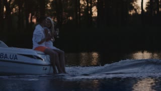 Young people drinking champagne on floating motor boat. Romantic weekend vacation on nature. Happy married couple in love resting together on yacht at night. Boating on river at night