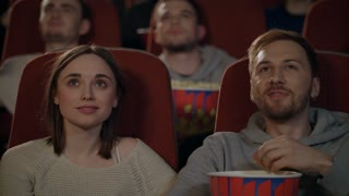 Young people enjoying film in cinema. Friends couple eating popcorn and watching movie in slow motion. Guy and girl watching movie in cinema. Love couple dating at cinema