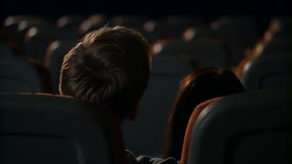 Young people kiss passionately at empty cinema hall. Love couple alone in empty cinema hall. Love couple kissing in cinema. Romantic date in movie theater in slow motion