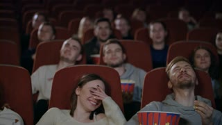 Young people laughing at cinema theater. Joyful people watching amusing comedy. Cheerful people smiling at movie theatre watching comedy film in slow motion. Friends spend weekend in cinema