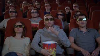 Young people sitting in movie theater watching 3D movie and eating popcorn in slow motion. Spectators watching movie in 3d glasses. Youth enjoying 3d film in cinema