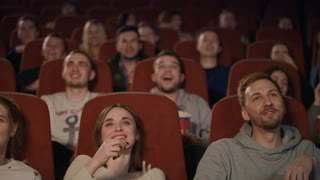 Young people watching movie in cinema theater. Emotional people eating popcorn. in cinema hall. Cinema people emotion in slow motion