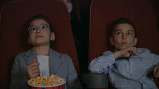 Young spectators watching movie at cinema. Boy and girl eating popcorn at cinema chairs. Beautiful children watching cartoon at movie theater. Movie children entertainment