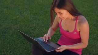 Young student with laptop on grass. Asian woman using laptop on grass. Young woman working with laptop computer on grass. Attractive woman laptop outdoors. Student working with notebook