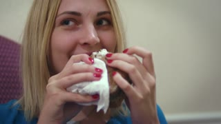 Young woman face biting tasty sandwich during lunch. Close up portrait hungry woman chewing sandwich and looking into camera. Woman fast food concept
