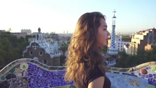 Young woman face turning around in Gaudi park. Happy girl spiniing and smiling. Beautiful tourist walking in Park Guell. Barcelona tourism travel concept