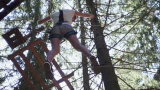 Young woman in protective equipment for climbing walking on rope on high in extreme park. Extreme sport for active people climbing trees in adventure park